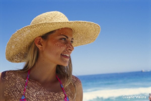 Close-up of a young woman smiling on the beach