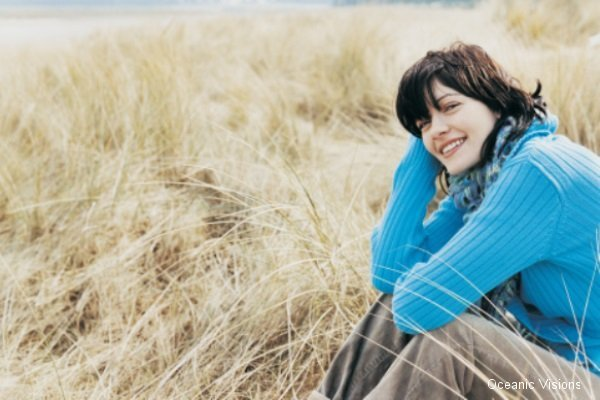 Woman Sitting on Dune Grass at Beach Smiling at Camera
