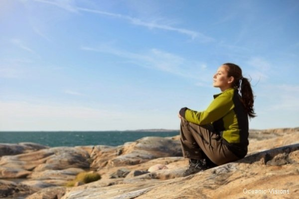 Sweden, Bohuslan, Styrso, Young woman relaxing on rock with seascape in background