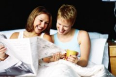 a young gay couple reading the newspapers in bed