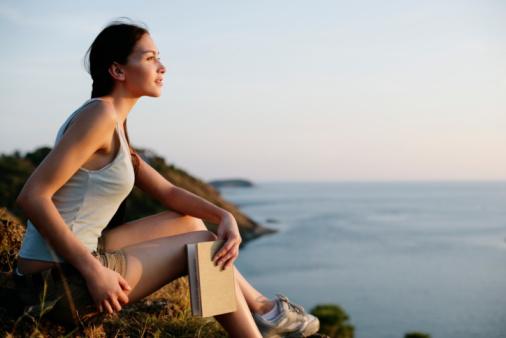 Woman sitting on rocks looking at ocean