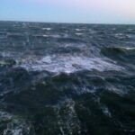 During a winter gale, foam-streaked whitecaps roll just off the starboard trawl deck.