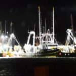 Fishing trawlers at night, lights burning, docked during ocean storm.